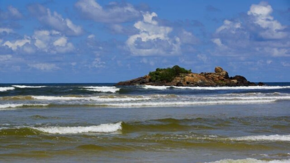 Das Meer, blauer Himmel, leicht schäumende Wellen, ein flacher Felsen im Hintergrund.