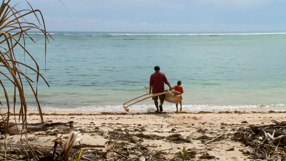 Ein Mann und ein Junge tragen ein Holzboot zum Meeresufer.