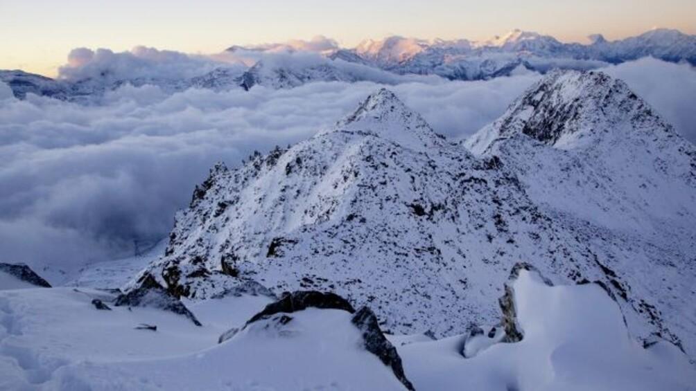 Schneeberge umzingelt von Wolken